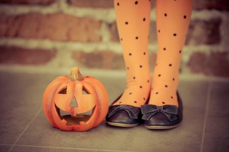 Funny child dressed witch costume holding pumpkin. Halloween holidays concept Standard-Bild