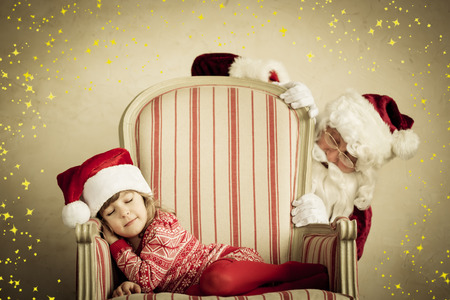 Santa Claus and sleeping child. Children dream. Christmas holiday concept. Xmas miracle Archivio Fotografico