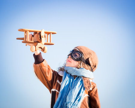 adventure holiday: Happy kid playing with toy wooden airplane against winter sky background Stock Photo