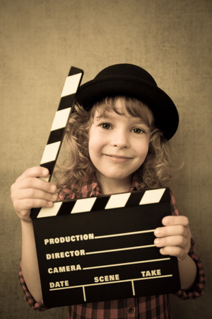 Happy kid holding clapper board against grunge wall background. Cinema concept photo