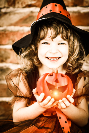 Funny child dressed witch costume holding pumpkin. Halloween holidays concept photo