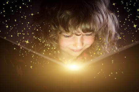 Happy kid reading magic book photo