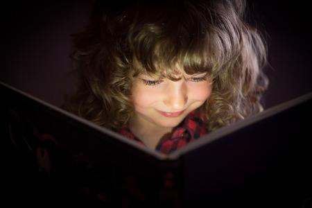 Feliz niño que lee el libro mágico Foto de archivo - 32056681