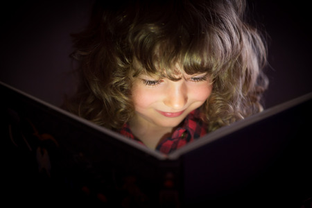 Happy child reading magic book photo