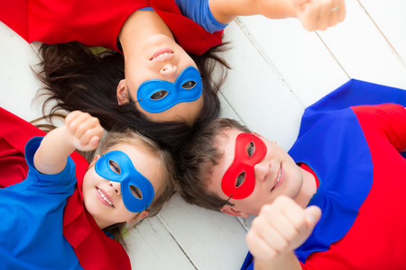 parent child: Family of superheroes lying on floor. Happy family having fun at home