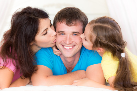 Woman and child kissing your father. Happy family having fun at home photo
