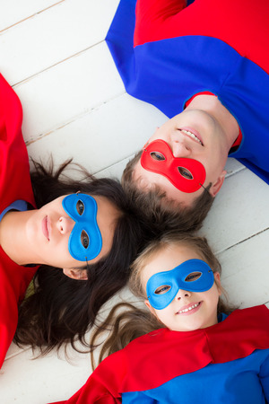of champions: Family of superheroes lying on floor. Happy family having fun at home