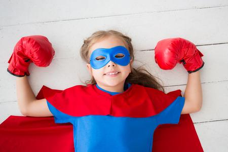 Superhero child lying on floor at home Фото со стока