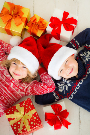 blue christmas background: Portrait of happy children with Christmas gift boxes. Two kids having fun at home