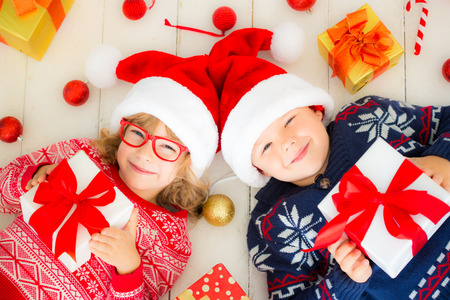Portrait of happy children with Christmas gift boxes and decorations. Two kids having fun at home photo