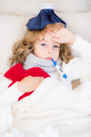 Niño enfermo con fiebre y una botella de agua caliente en el hogar Foto de archivo