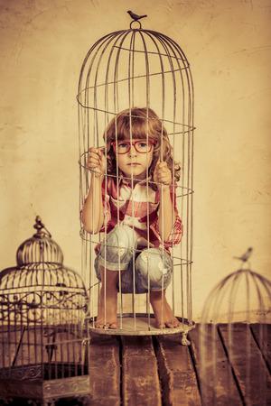 Sad child in steel cage. Human rights concept Foto de archivo