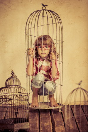 Sad child in steel cage. Human rights concept Stockfoto