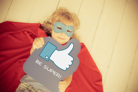 Superhero child holding LIKE sign. Social media concept. Retro toned photo