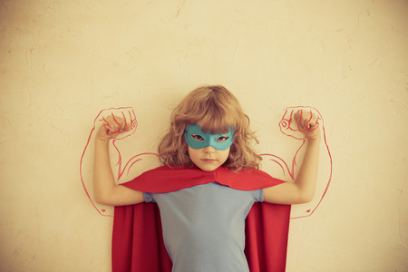 Strong superhero child with drawn muscles. Girl power and feminism concept 스톡 콘텐츠