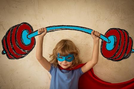 imaginacion: Ni�o Superh�roe contra la pared de fondo del grunge. El �xito y el concepto del ganador Foto de archivo