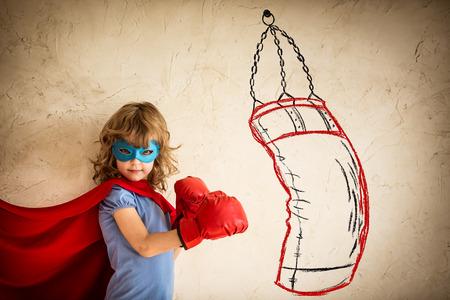 Superhero jong geitje in rode bokshandschoenen ponsen op de getekende tas. Winnaar en succes concept Stockfoto