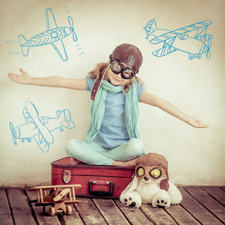 Happy child playing with toy airplane at home. Retro toned photo