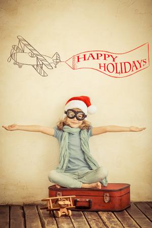viagem: Criança feliz no chapéu de Papai Noel que joga com avião de brinquedo em casa. Retro tonificado