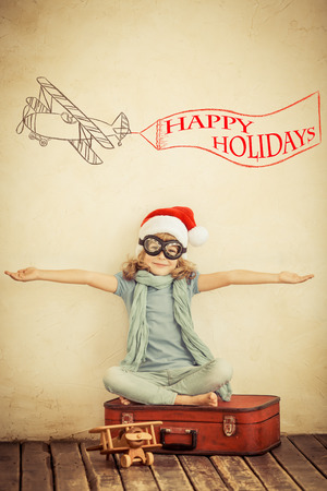 Happy child in Santa Claus hat playing with toy airplane at home. Retro toned photo