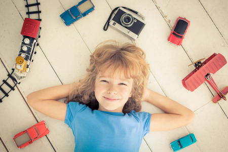 Child with vintage toys at home. Girl power and feminism concept