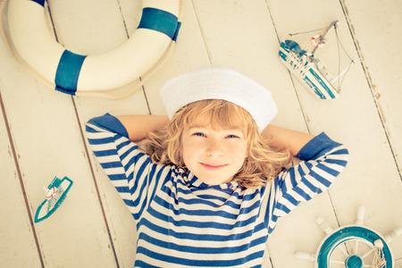 sailor: Cabrito feliz que juega con el barco de vela del juguete en casa. Viajes y aventura concepto