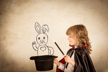 mago: Mago del ni�o que sostiene un sombrero de copa con conejo dibujado contra el fondo del grunge. Foco en el sombrero Foto de archivo