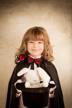 mago: Mago del niño que sostiene un sombrero de copa con un conejo de juguete. Concepto de éxito