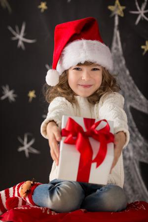 Niño que sostiene regalo de Navidad. Concepto de vacaciones de Navidad Foto de archivo