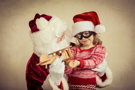 Santa Claus and child playing with vintage wooden plane at home. Christmas gift. Family holiday concept photo