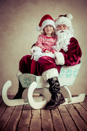 Santa Claus and child riding on sleigh. Christmas concept. Family holiday