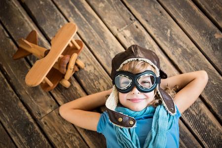 pilotos aviadores: Piloto Ni�o con el juguete avi�n de la vendimia en el fondo del grunge de madera Foto de archivo