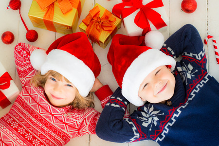 christmas box: Portrait of happy children with Christmas decorations. Two kids having fun at home