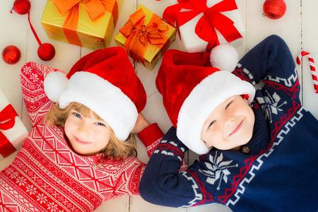Portret van gelukkige kinderen met kerstversieringen. Twee kinderen plezier thuis
