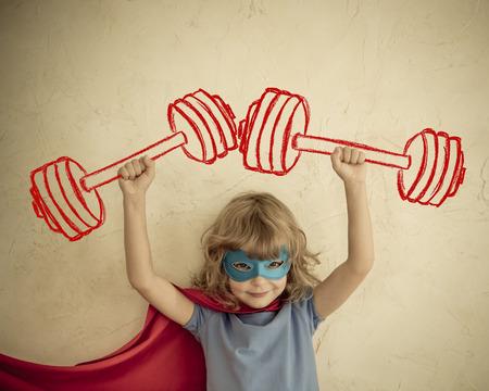 Superhero kid having fun at home. Retro toned Foto de archivo