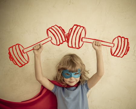 Superhero kid having fun at home. Retro toned Stock Photo