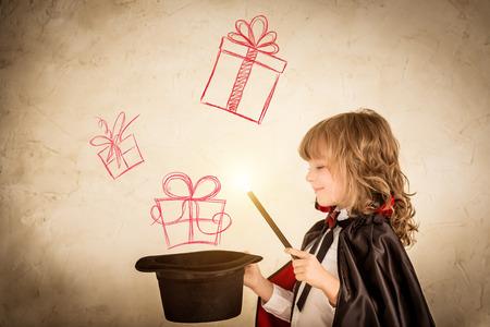 Mago del niño que sostiene un sombrero de copa con cajas de regalo elaborados. Concepto de vacaciones de navidad Foto de archivo