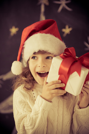holding a christmas ornament: Child holding Christmas gift.