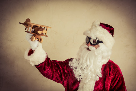 Santa Claus senior man playing with vintage wooden airplane against grunge background.