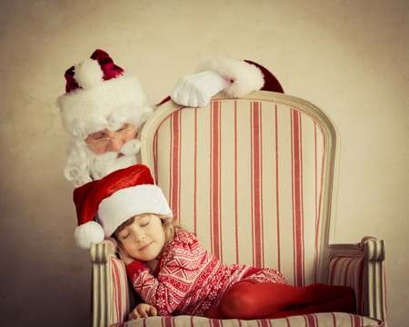 Santa Claus and child at home.  photo