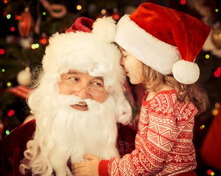 Santa Claus y el niño en el hogar. Regalo de Navidad. Concepto de vacaciones de la familia