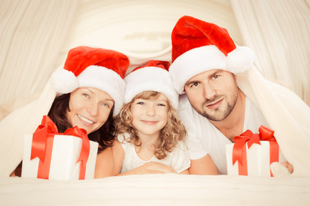 Happy family at home. Mother, father and child with Christmas gift. Xmas holiday concept photo