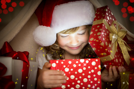 Child holding Christmas gift. Xmas holiday concept Banco de Imagens