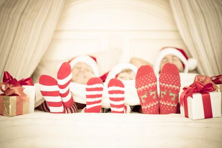 vintage: Lycklig familj hemma. Mamma, pappa och barn med julklapp. Vintersemester koncept Stockfoto