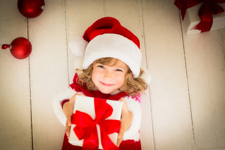 gold gift box: Child holding Christmas gift. Xmas holiday concept Stock Photo
