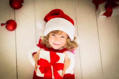 Niño que sostiene regalo de Navidad. Concepto de vacaciones de Navidad Foto de archivo - 32862100