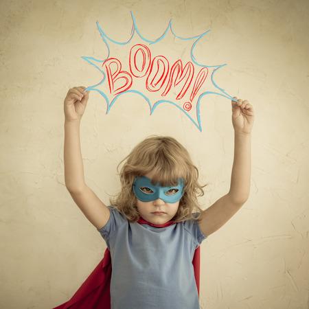 feminism: Superhero child against grunge wall background