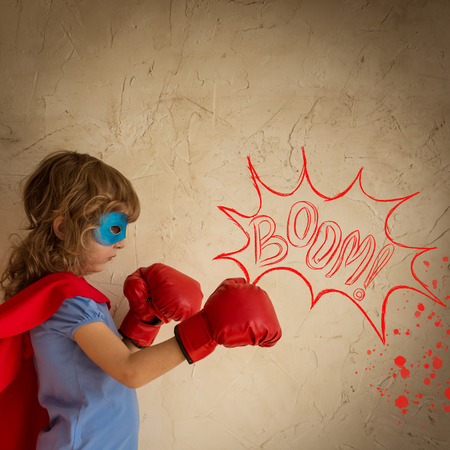girl punch: Superhero child against grunge wall background