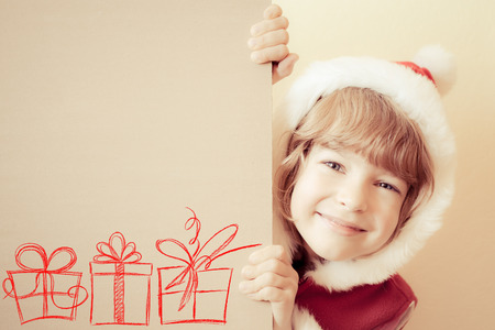 Child holding Christmas card blank with drawn gift boxes. Xmas holiday concept