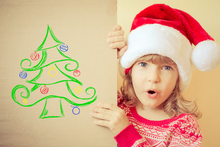holding a christmas ornament: Surprised child holding Christmas card with drawn Xmas tree. Winter holiday concept